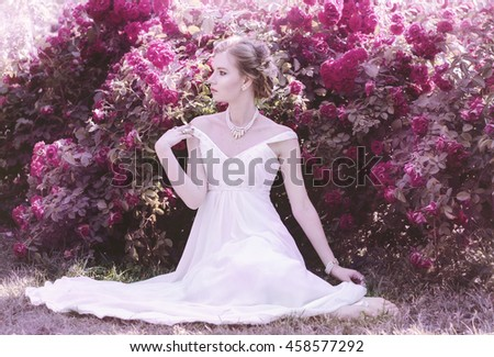 portrait of a sweet, attractive, gentle, romantic, sensual girl in a romantic hairstyle, wearing a white dress. She is sitting on the grass next to kustoi blooming roses. Bride for a walk - stock photo