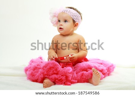 Portrait of a sweet infant wearing a pink tutu and headband bow - stock photo