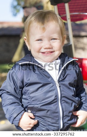 Portrait of a sweet one year old baby girl in a park on a autumn day