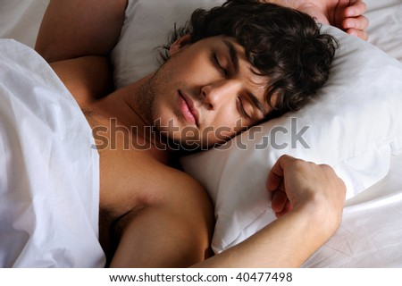 Portrait of a sweet sleeping young beautiful   man lying on back - stock photo