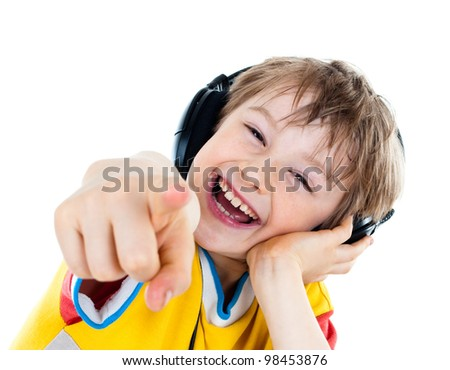 Portrait of a sweet young boy listening to music on headphones against white background - stock photo