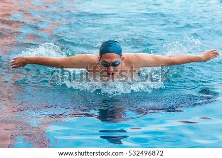 Portrait of a swimmer in cap breathing performing the butterfly stroke