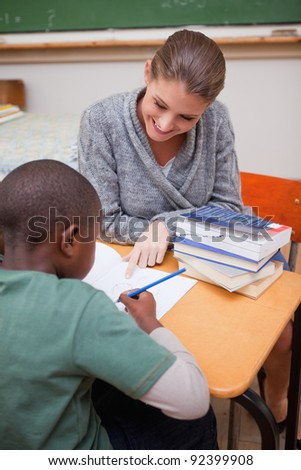Portrait of a teacher explaining something to a pupil in a classroom - stock photo