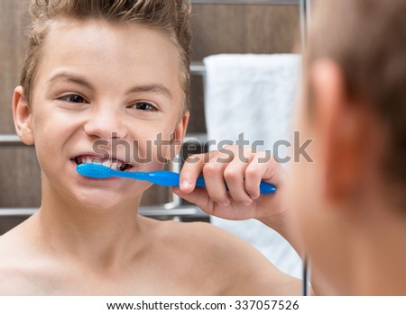 Portrait of a teen boy in the bathroom brushing his teeth - stock photo