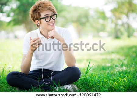 Portrait of a teenage boy listening to mp3 player outdoors - stock photo