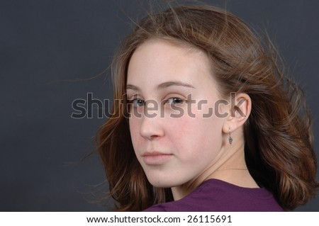 Portrait of a teenage girl against a black background - stock photo