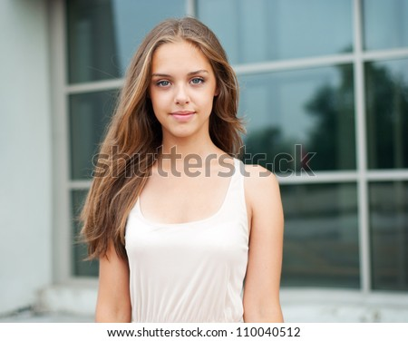 Portrait of a teenage girl against a large window - stock photo