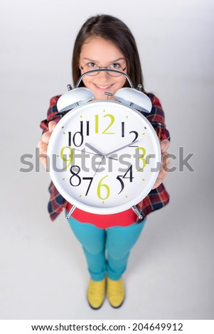 Portrait of a teenage girl holding a big clock. Upper recourse. Gray background