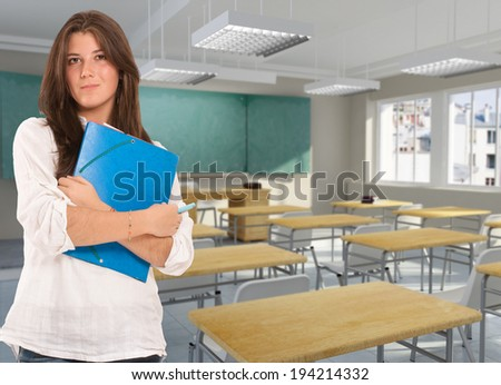 Portrait of a teenage girl holding a binder in a classroom - stock photo