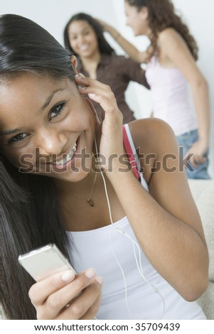 Portrait of a teenage girl listening to music with an MP3 player and smiling - stock photo