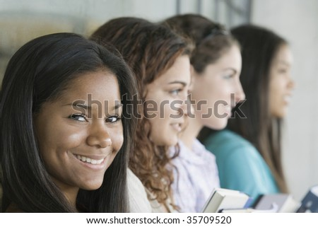 Portrait of a teenage girl smiling with her friends beside her - stock photo