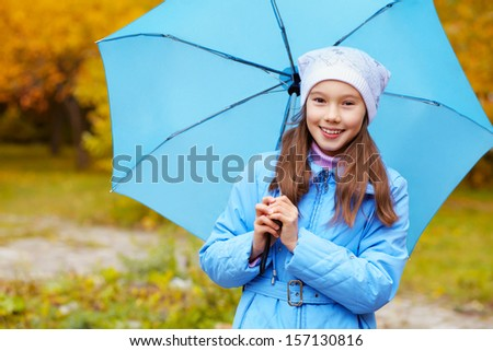 Portrait of a teenage girl walking around in the park on a background of yellow autumn leaves