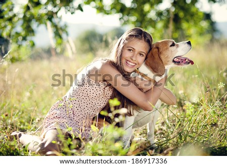 Portrait of a teenage girl with her beautiful dog outdoors - stock photo