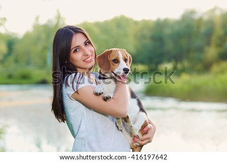 Portrait of a teenage girl with her dog outdoors. - stock photo