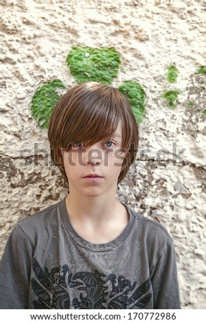 portrait of a teenager boy with green shamrock behind his head.