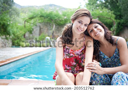 Portrait of a teenager daughter and her mother sitting and smiling during a summer holiday in a vacation home green garden at the edge of a swimming pool, relaxing together. Outdoors lifestyle. - stock photo