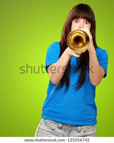 portrait of a teenager playing trumpet on green background - stock photo