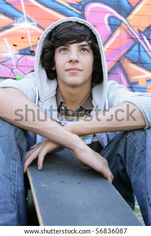 Portrait of a teenager sitting in front of a wall of graffiti with a skateboard - stock photo