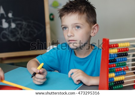 Portrait of a thinking school boy working on math homework with an abacus