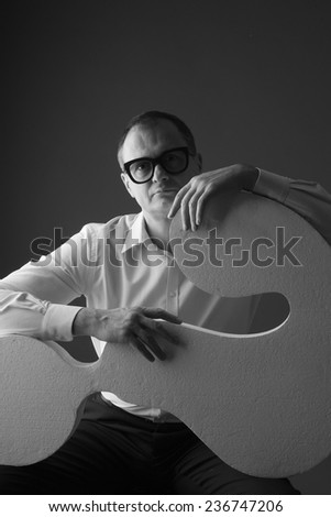 Portrait of a thoughtful businessman holding a question mark model, problem solving concept; monochrome - stock photo