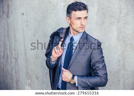 Portrait of a thoughtful businessman holding jacket on shoulder and looking away - stock photo