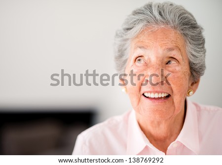 Portrait of a thoughtful elder woman smiling - stock photo