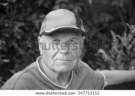 Portrait of a thoughtful senior looking at camera, outdoor shot in black and white - stock photo