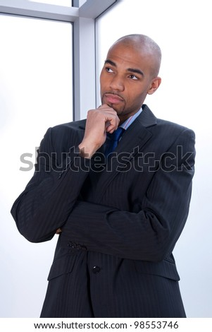 Portrait of a thoughtful young businessman beside a window. - stock photo