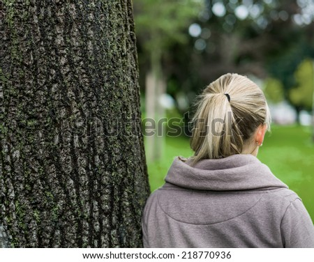 portrait of a thoughtful young woman from behind - stock photo