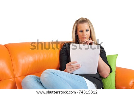 Portrait of a thoughtful young woman lying on couch reading a paper - stock photo