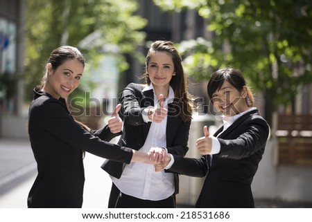 Portrait of a three happy business woman all with there thumbs-up.  - stock photo