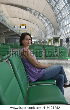 """Portrait of a tired and sad adult woman. Airport waiting room. """"Real People"""" series. - stock photo"""
