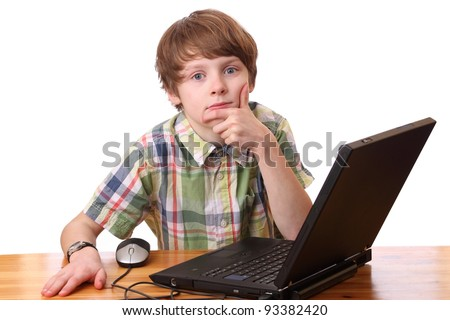 Portrait of a tired and upset boy working on a laptop computer