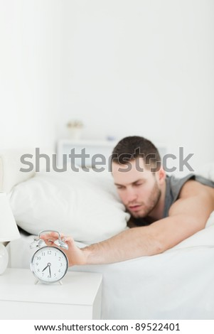 Portrait of a tired man being awakened by an alarm clock in his bedroom - stock photo