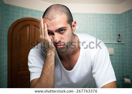 Portrait of a tired man looking in the mirror in the bathroom - stock photo