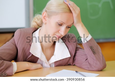 Portrait of a  tired teacher  in a classroom - stock photo
