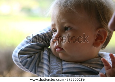 Portrait of a toddler baby looking sideways  - stock photo