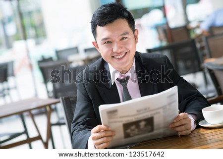 Portrait of a toothy entrepreneur reading newspaper during the break