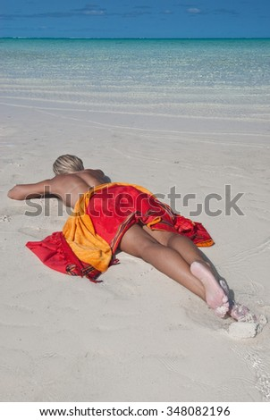 Portrait of a topless blonde woman relaxing on a pristine beach with a bright red sarong  - stock photo