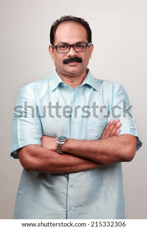 Portrait of a traditionally dressed Indian man with folded hands - stock photo