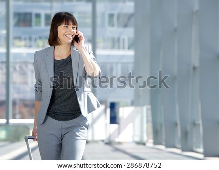 Portrait of a traveling business woman talking on cell phone at airport - stock photo