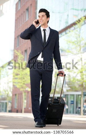 Portrait of a traveling businessman talking on mobile phone - stock photo