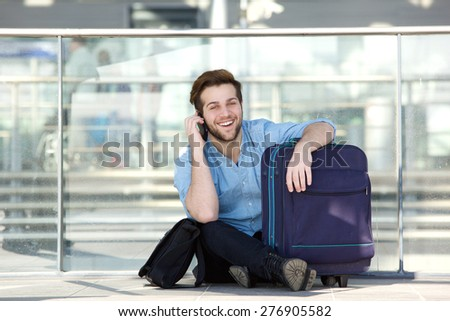 Portrait of a traveling man sitting on floor at station with bag and mobile phone  - stock photo