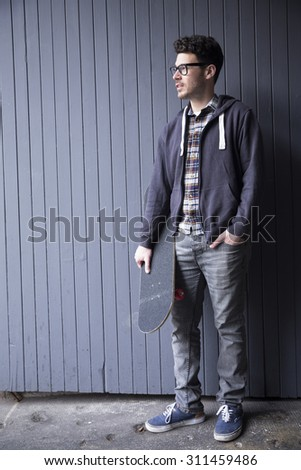 Portrait of a trendy urban man holding a skateboard.