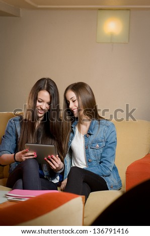 Portrait of a two beautiful teen girls having fun together with tablet computer. - stock photo