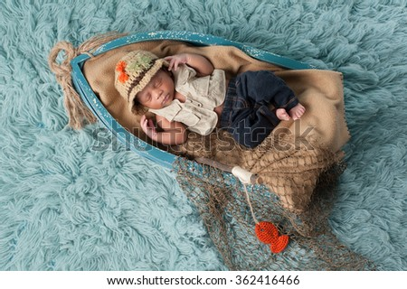 Portrait of a two week old newborn baby boy. He is sleeping in a miniature boat and wearing a fisherman's hat, vest and jeans. Shot in the studio on an aqua colored flokati rug. - stock photo