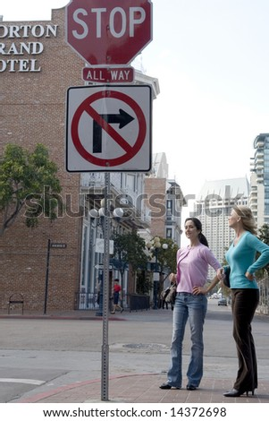 Portrait of a two women standing in front of a street sign - stock photo