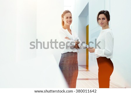 Portrait of a two young female professional staff using touch pad to discuss work issues during break between conference, intelligent women ceo standing with digital tablet in modern office interior  - stock photo