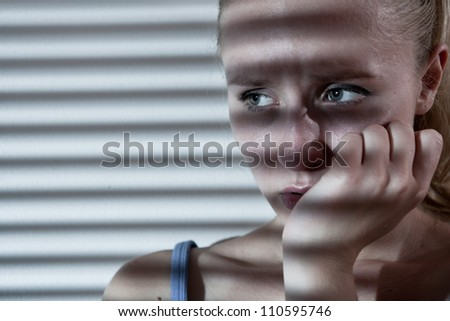 Portrait of a unhappy and depressed young woman in depressive stripe environment, desaturated image - stock photo