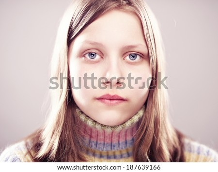 Portrait of a unhappy teen girl, studio shot - stock photo